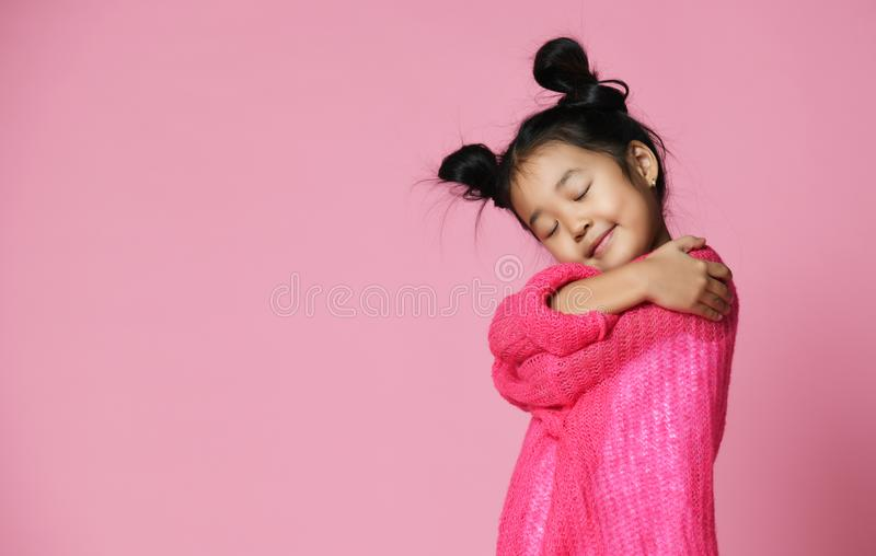 有闭合的眼睛的亚裔孩子女孩在桃红色毛线衣拥抱和梦想 免版税库存图片