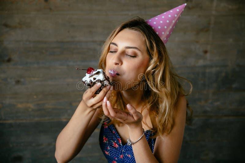 有闭合的眼睛的俏丽的女孩吃巧克力蛋糕的 免版税图库摄影