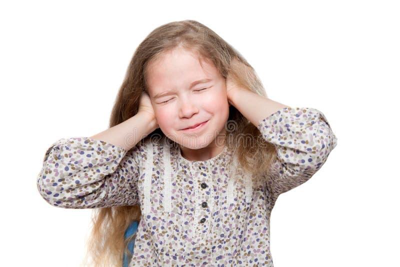 有闭合的眼睛的女孩用手盖耳朵 免版税库存图片