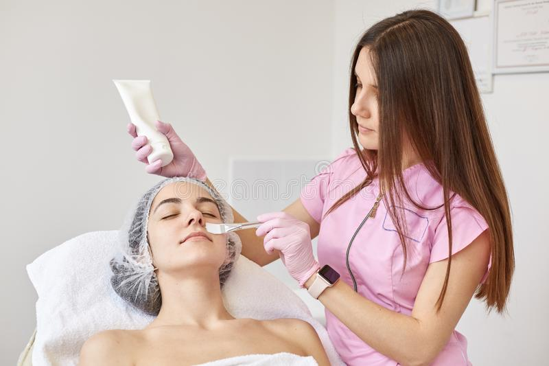 有闭合的眼睛的平安的客户有秀丽做法,放置安静在化妆椅子,有在头的医疗盖帽 ?? 免版税库存图片
