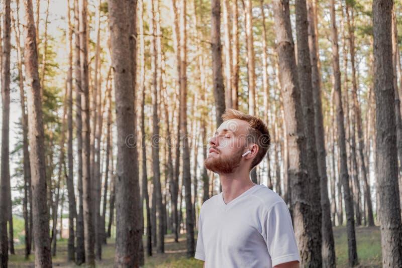 有闭合的眼睛的年轻人享受自然在步行期间或跑步在森林里的 免版税库存照片