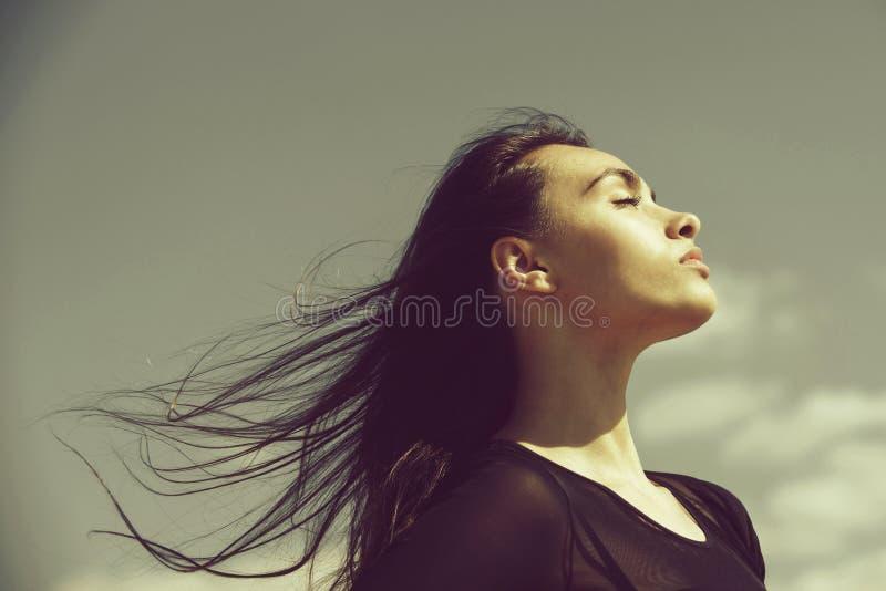 有闭合的眼睛的放松与挥动的,长发妇女 免版税库存照片
