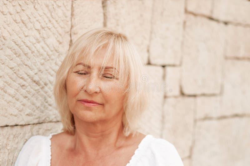 有闭合的眼睛的放松美丽的成熟的妇女作梦和 库存图片