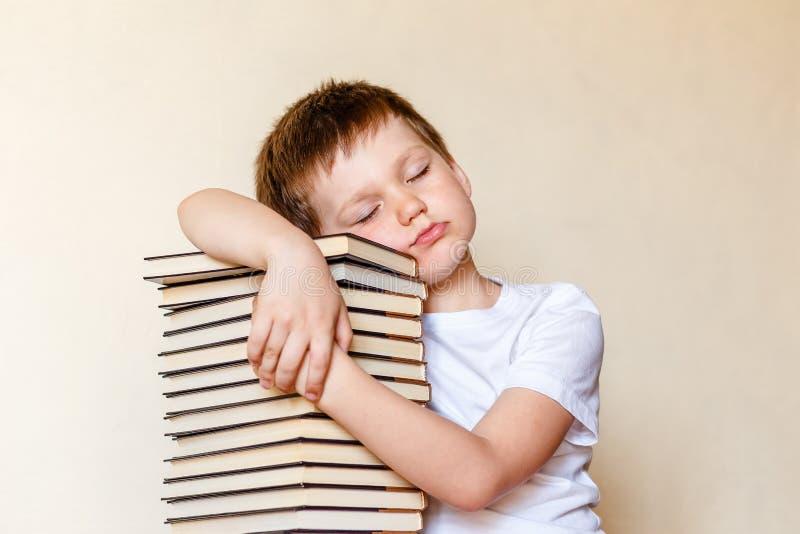 有闭合的眼睛的男孩睡觉在堆的书 免版税库存图片