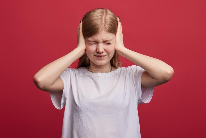 有闭合的眼睛的被挫败的女孩设法不听她的父母的丑闻 库存照片