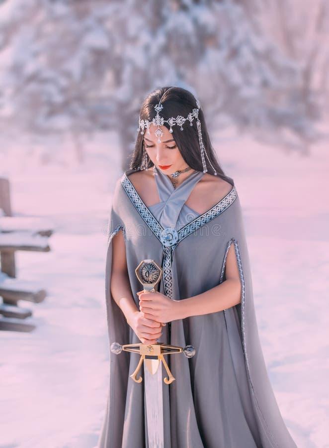 有闭合的眼睛的迷人的甜深色头发的女孩读祷告给战争之神在可怕的战斗,典雅的公主前 免版税图库摄影