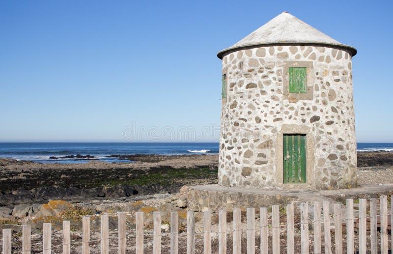 有闭合的绿色门的被放弃的老在大西洋海岸,葡萄牙的灯塔和窗口 在木篱芭后的灯塔 免版税库存图片