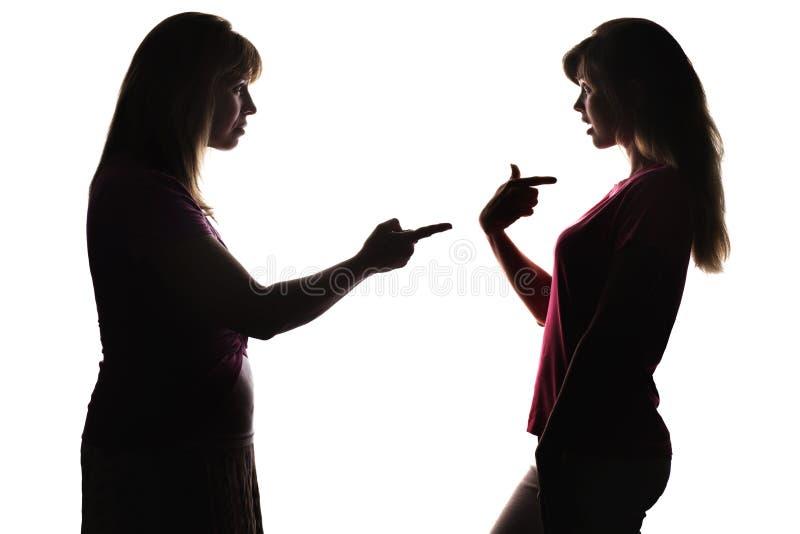 有问题的联系剪影在母亲和少年,妈妈之间的戳手指,责备女儿 免版税库存图片