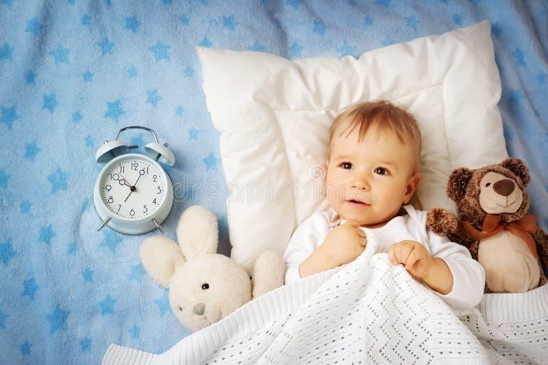 有闹钟的一个岁婴孩 库存照片