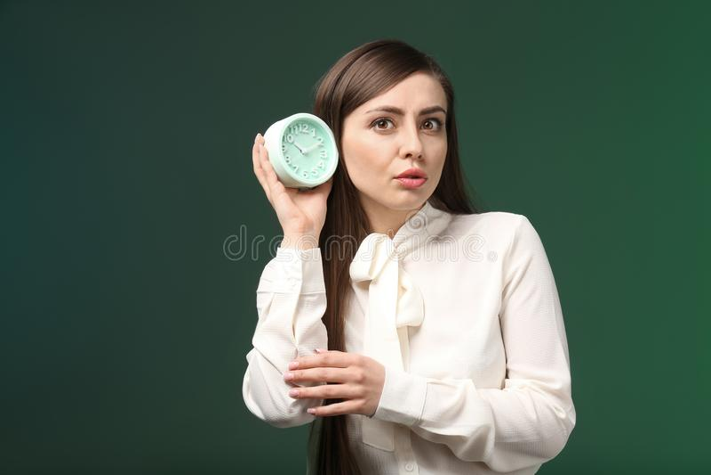 有闹钟的妇女在颜色背景 E 库存图片