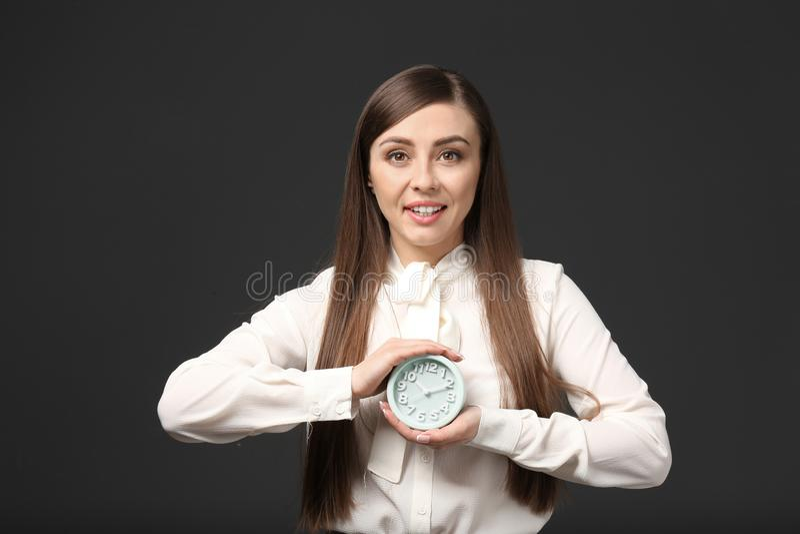 有闹钟的妇女在颜色背景 E 库存照片