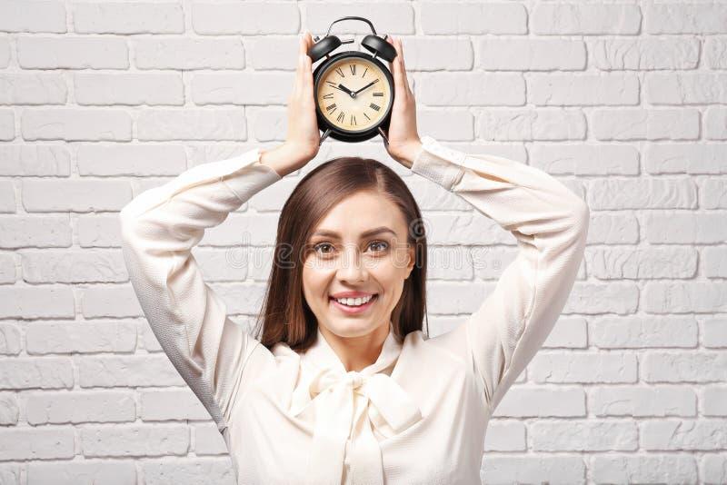 有闹钟的妇女对白色砖墙 E 库存图片