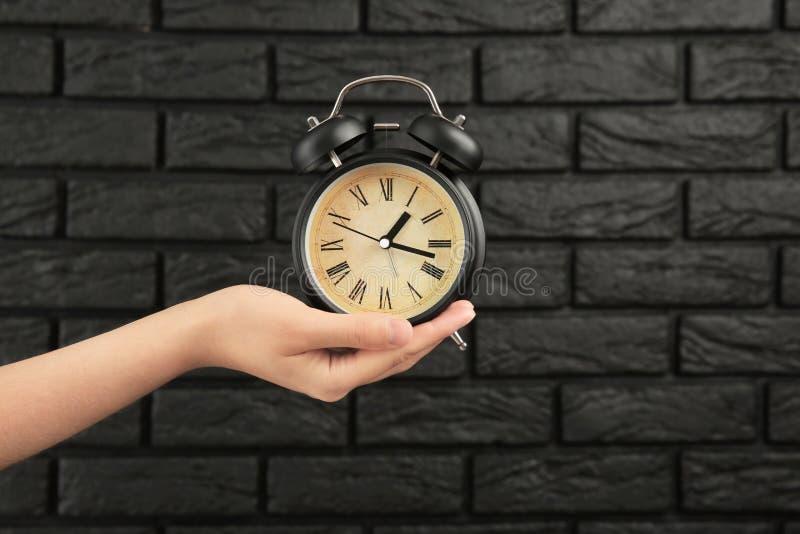 有闹钟的妇女对砖墙 E 图库摄影