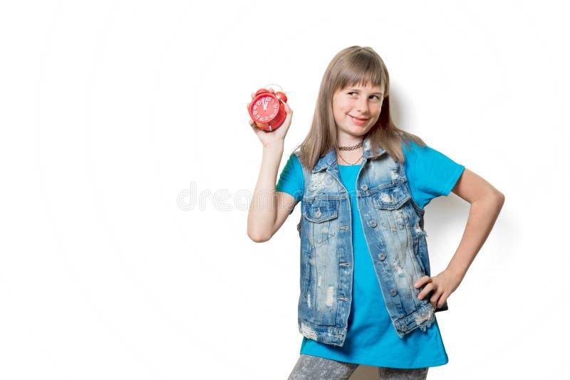 有闹钟的微笑的十几岁的女孩 库存照片