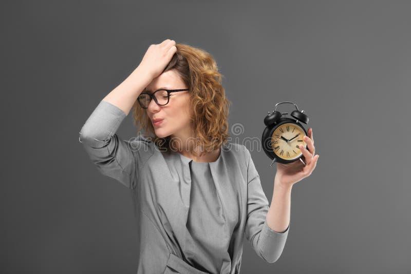 有闹钟的成熟妇女在灰色背景 E 库存照片