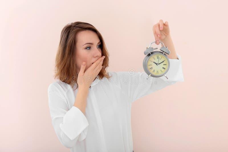 有闹钟的成熟妇女在颜色背景 E 库存照片