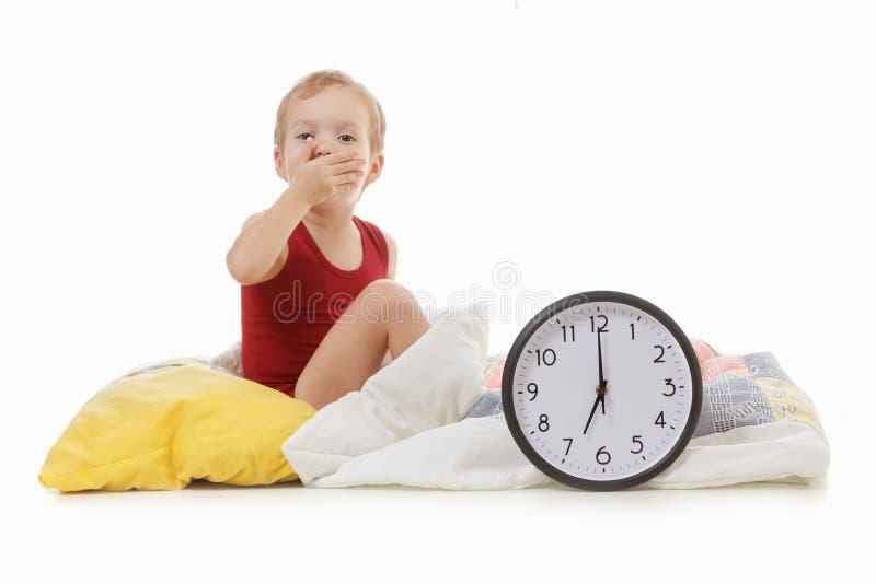 有闹钟的男孩在床上,叫醒概念 免版税图库摄影