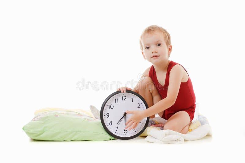 有闹钟的男孩在床上,叫醒概念 库存照片