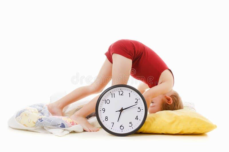 有闹钟的男孩在床上,叫醒概念 免版税库存照片