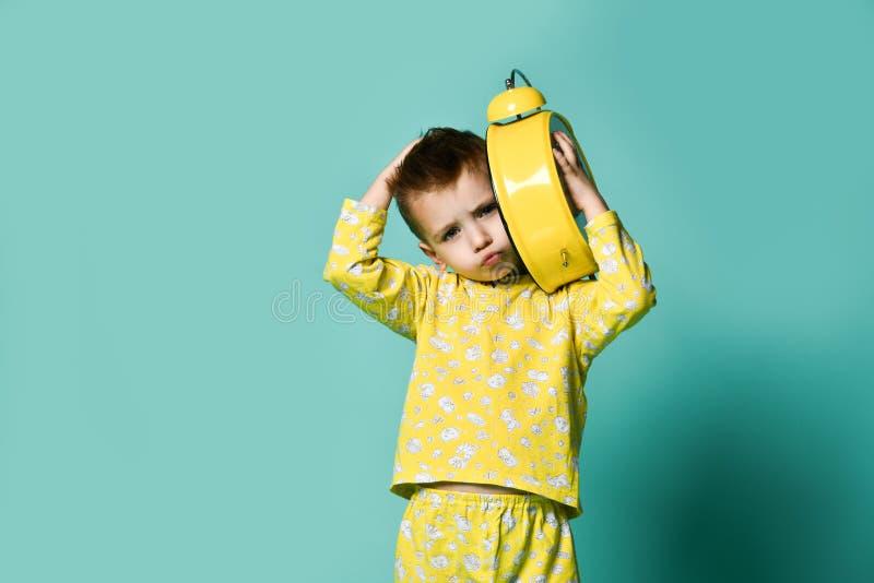 有闹钟的逗人喜爱的小男孩,隔绝在蓝色 指向闹钟的滑稽的孩子早晨 库存照片