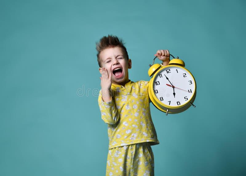 有闹钟的逗人喜爱的小男孩,隔绝在蓝色 指向闹钟的滑稽的孩子7点早晨 图库摄影