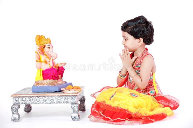有阁下ganesha和祈祷的小印地安女孩孩子,印地安ganesh节日 免版税库存照片