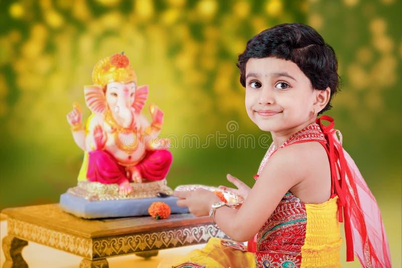 有阁下ganesha和祈祷的小印地安女孩孩子,印地安ganesh节日 免版税图库摄影