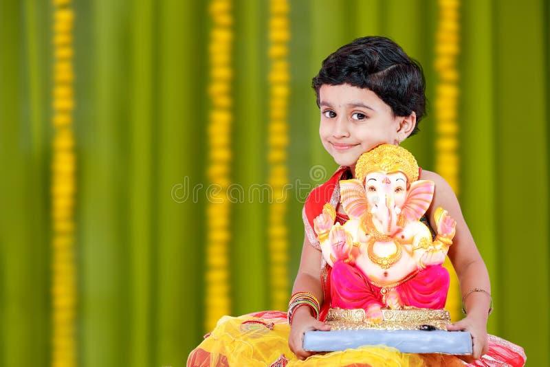有阁下ganesha和祈祷的小印地安女孩孩子,印地安ganesh节日 免版税库存图片