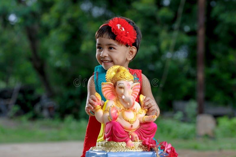 有阁下ganesha和祈祷的小印地安女孩孩子,印地安ganesh节日 库存照片