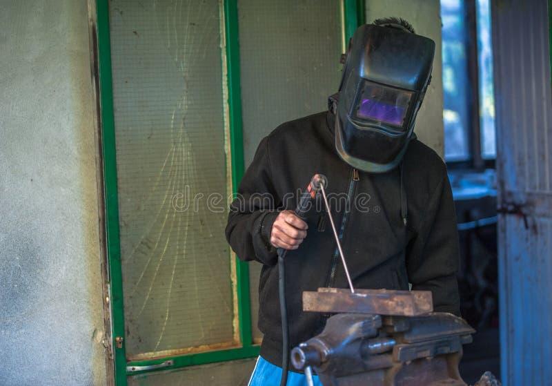 有防护手套和防毒面具焊接金属零件的工作者在车间 免版税库存图片