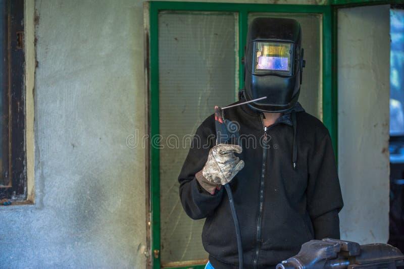 有防护手套和防毒面具焊接金属零件的工作者在车间 免版税图库摄影