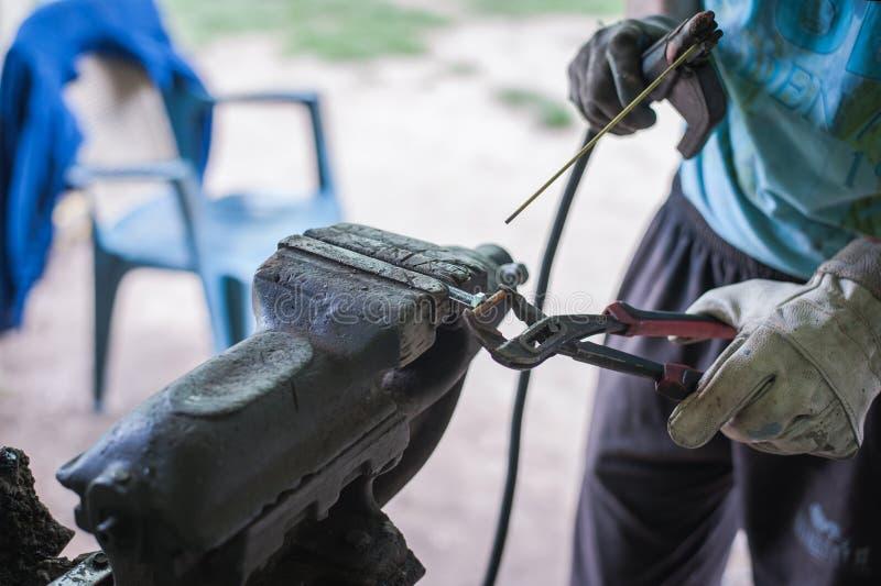 有防护手套焊接金属零件的工作者在车间 免版税图库摄影