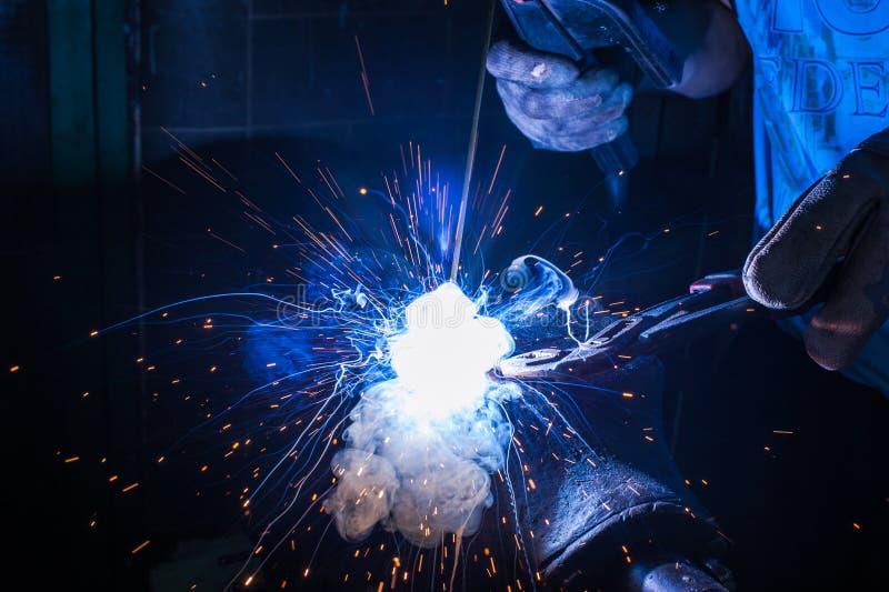 有防护手套焊接金属零件的工作者在车间 免版税库存照片