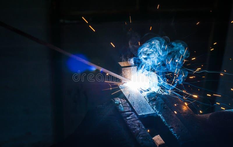 有防护手套焊接金属零件的工作者在车间 库存图片