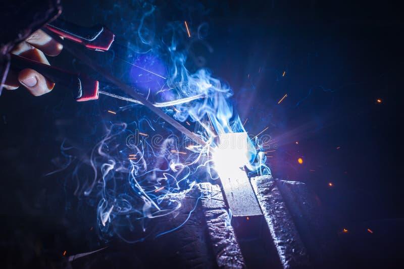 有防护手套焊接金属零件的工作者在车间 库存照片