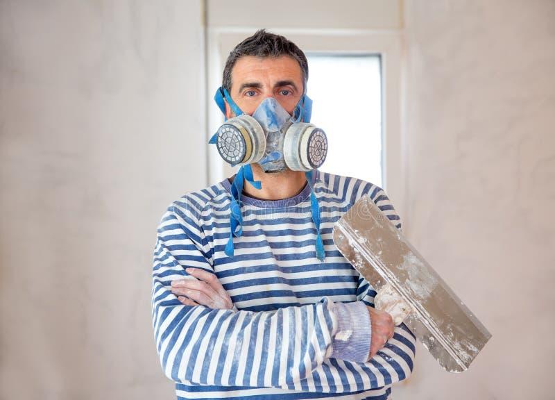 有防毒面具和修平刀的滑稽的涂灰泥的人泥工 图库摄影