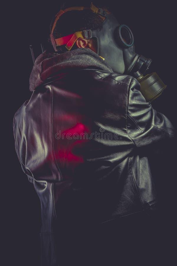 有防毒面具和枪的人,穿戴在黑皮夹克 免版税库存图片