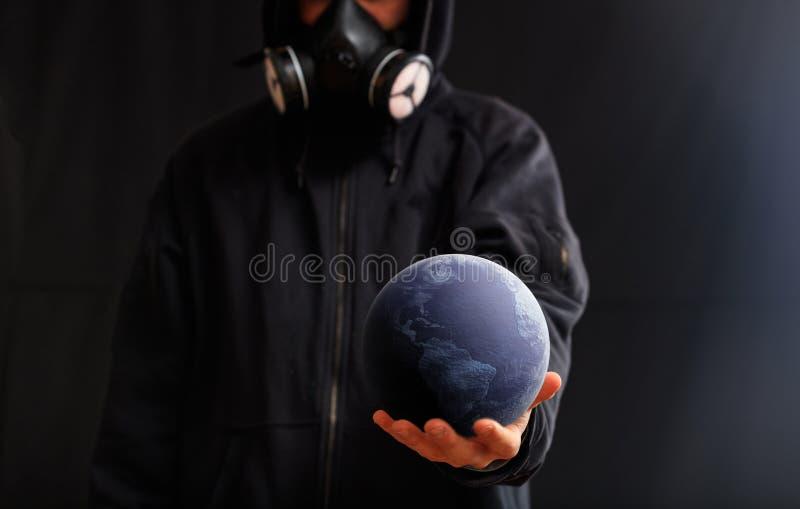 有防毒面具的人在他的手上的拿着地球地球,黑暗的背景 3d?? 库存图片