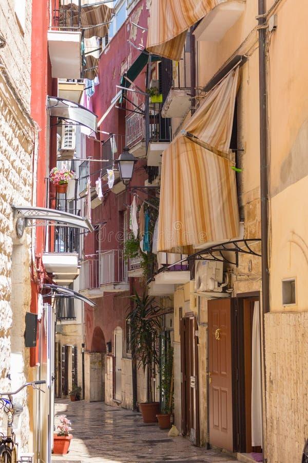 有阳台、干燥衣裳和自行车的狭窄的意大利街道 传统地中海建筑学 意大利镇地标 免版税库存照片