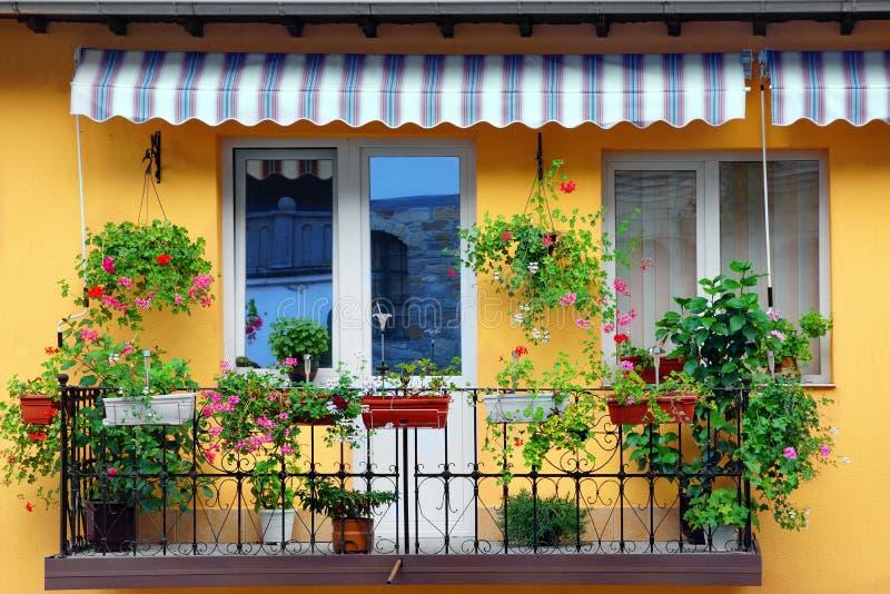 有阳台用花装饰的庭院的黄色大厦墙壁 免版税库存图片