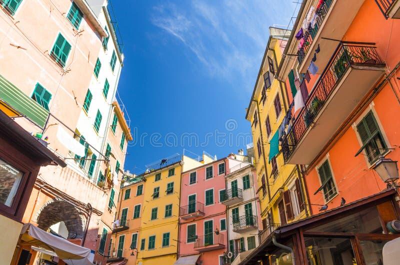 有阳台的多彩多姿的五颜六色的大厦房子和在里奥马焦雷典型的传统鱼狭窄的街道上的快门窗口  免版税库存图片