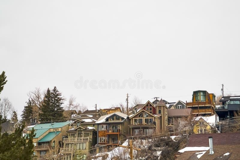 有阳台的小山家和反对多云天空的多雪的屋顶在冬天 免版税库存图片