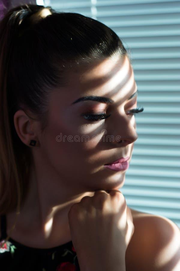 有阴影的想法的急切妇女在软百叶帘的面孔在窗口和手的在下颌 免版税图库摄影