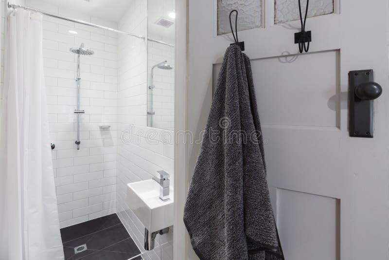 有阵雨和垂悬的毛巾的小白色铺磁砖的ensuite卫生间 免版税图库摄影