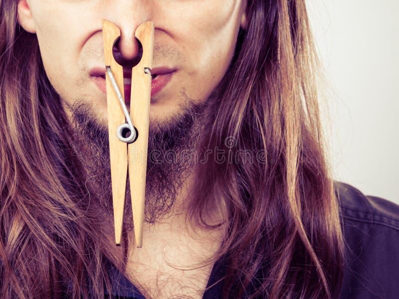 有阻塞的鼻子的人由晒衣夹 免版税图库摄影