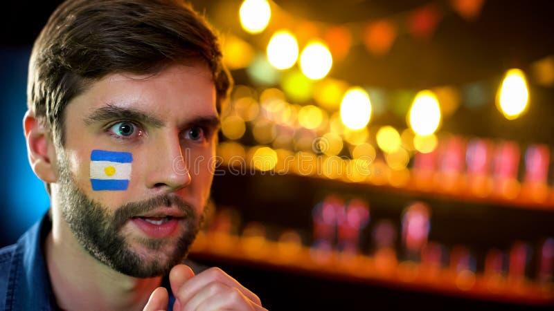 有阿根廷旗子的急切爱好者在面颊殷勤地观看足球赛的 库存照片