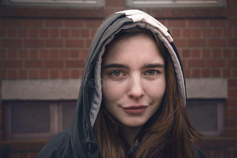 有附头巾皮外衣的微笑的年轻女人 免版税库存照片