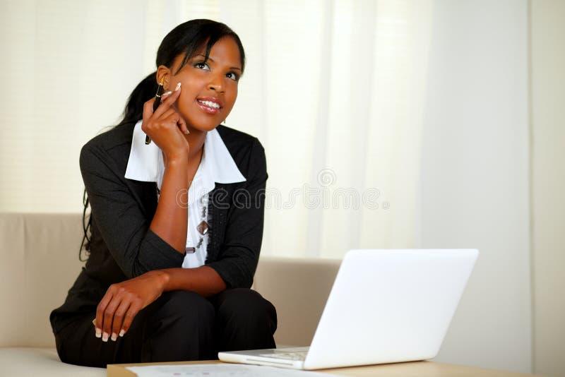 有附注和膝上型计算机的沉思女实业家 免版税库存图片