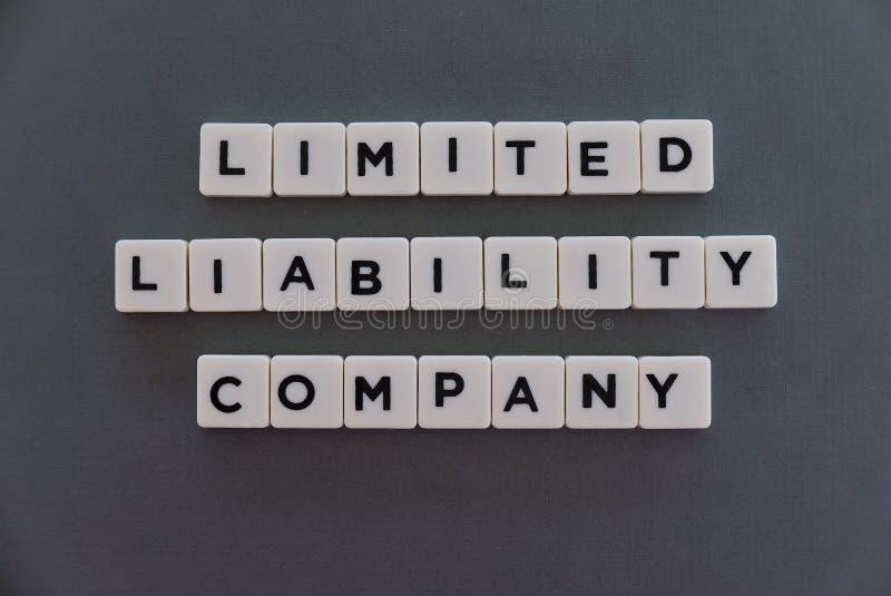 有限公司(LLC)词由方形的信件词制成在灰色背景 库存照片