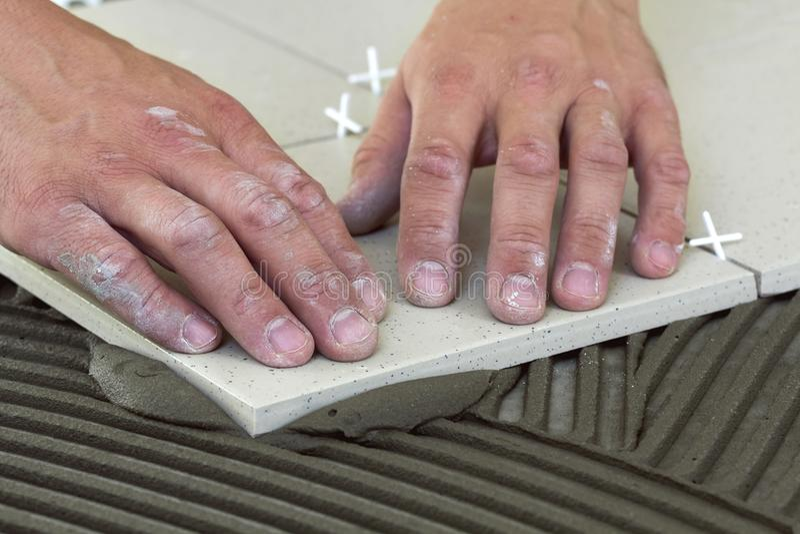 有陶瓷砖和工具的工作者手为铺磁砖工 地垫 免版税图库摄影